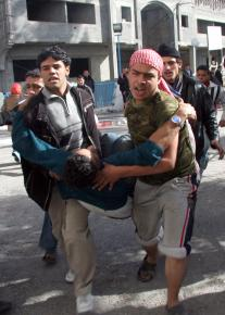 Palestinians in Gaza City carry a victim of the Israeli assault to Al Shifa hospital